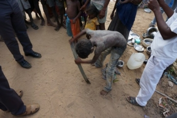 One of the rescued boys uses a steel strip to demonstrate the work the families were forced to do daily.