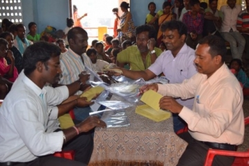 Government officials prepare the release certificates and cash that each survivor will receive.