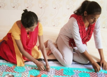 Women carefully piece together quilts for survivors.