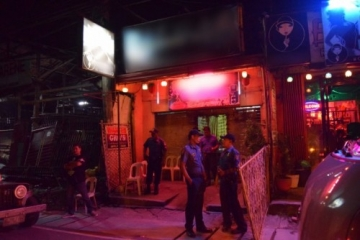 Police stand watch outside the karaoke bar where young women were rescued from trafficking.