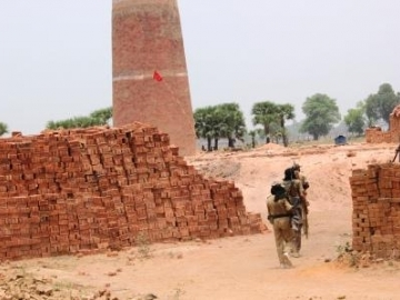 Local authorities lead the rescue team into the brick factory where families were held in slavery.