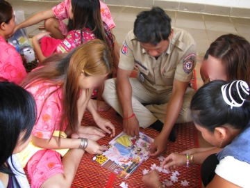 Anti-trafficking police have been trained on investigations, interview techniques, and victim-sensitive procedures. Here, a police officer helps survivors of a brothel put together a princess puzzle in 2009.