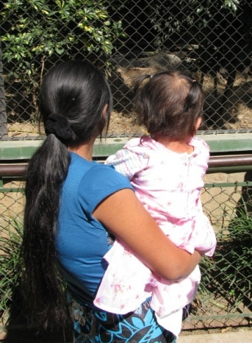 "Iris, now 17 years old, holds her daughter at the zoo. IJM organized a ""Day of Joy"" in January 2014 for girls who are survivors of sexual violence and are receiving care from our social workers."