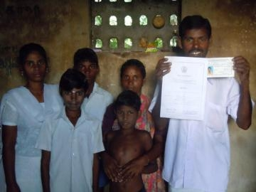 Kutty and his family, proudly displaying official documents certifying him as a local government official