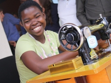 IJM presented Mimi with a sewing machine after she finished a yearlong training course. Now she can provide for herself – and make sure her daughter has a bright future.
