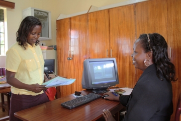 Mukono staff member assisting client using newly installed case management system.
