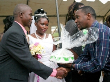 IJM Kampala's Joshua Niyo, right, congratulates one of the newlywed couples.