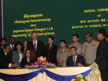 IJM Cambodia Director Christa Hayden Sharpe (front, left) and Secretary of State H.E Teng Savong sign the official renewal of the memorandum of agreement that formalizes how IJM will support Cambodian law enforcement in combatting human trafficking.