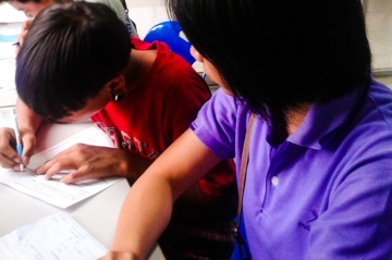 An IJM aftercare staff member helps Dang* apply for schooling.