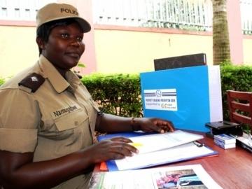 Property Grabbing Prevention Police Desk Officer Namubagwe at her new desk provided by IJM