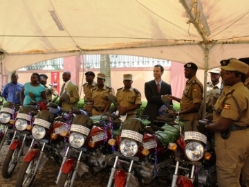 The Property Grabbing Prevention police officers stand with their new bikes that will allow them to travel for work. IJM Uganda Director Jesse Rudy and the Assistant Inspector General shake hands on the right.