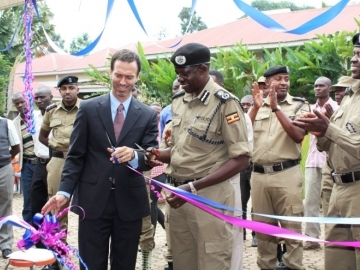 IJM Uganda Director Jesse Rudy and the Assistant Inspector General cut the ribbon at the December 2013 event launching the new Property Grabbing Prevent Police Desks within the Ugandan Police