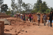 An IJM Bangalore lawyer leads the families out of the brick factory where they had been enslaved.