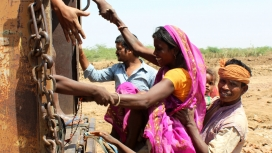 A woman boards a truck that will bring her out of the brick kiln, into safety.